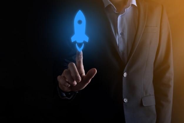 Il concetto di affari di avvio, uomo d'affari che tiene tablet e icona razzo sta lanciando e volando fuori dallo schermo con connessione di rete sulla parete scura.