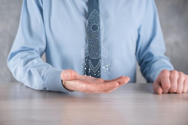 Avvio del concetto di business, uomo d'affari che tiene un lancio di un razzo trasparente.