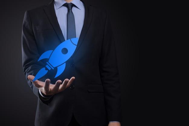 Il concetto di business di avvio, tenendo l'icona del razzo sta lanciando e volando in volo