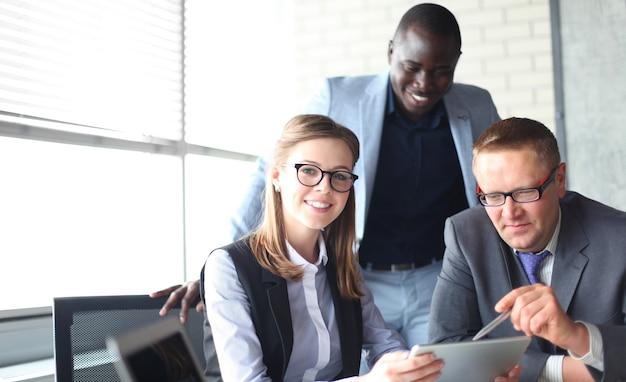 Startup business team in riunione in un moderno e luminoso ufficio di brainstorming interno, lavorando su laptop e tablet computer