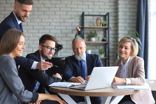Squadra di affari di avvio sulla riunione nell'interno luminoso moderno dell'ufficio e sul lavoro al computer portatile.
