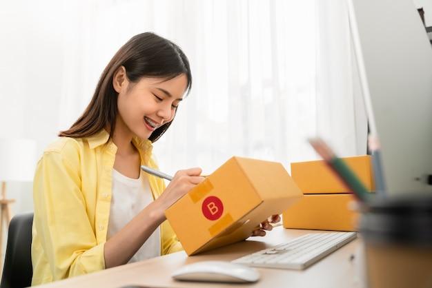 Avvio di una piccola impresa concetto, giovane donna proprietario che lavora e imballaggio sulla scatola per il cliente a casa in ufficio