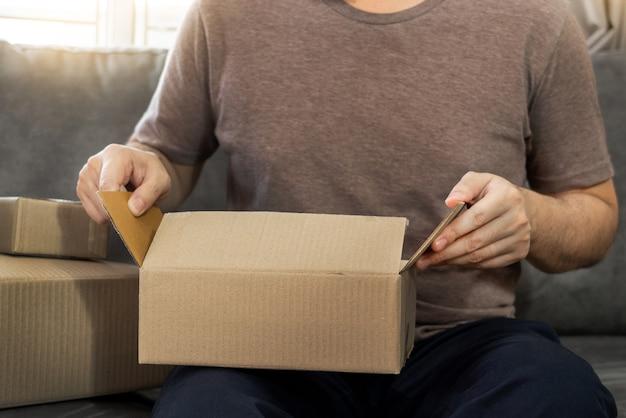 Avvio di piccole imprese imprenditore pmi, giovane uomo asiatico che lavora con computer portatile e scatola di imballaggio di consegna