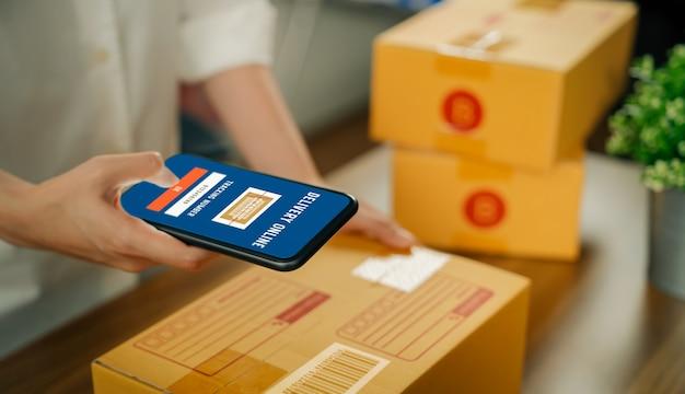 Avvio di una piccola impresa, proprietaria di donna che utilizza lo smartphone esegue la scansione del codice a barre per salvare le informazioni nel sistema di spedizione e imballare i prodotti di consegna della scatola ai clienti dall'ordinazione online.