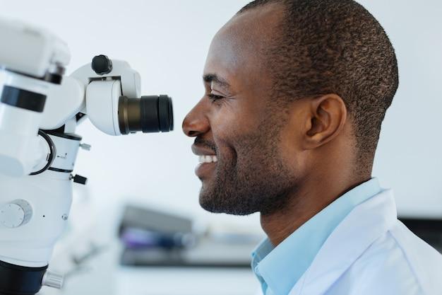 Dispositivo all'avanguardia. la vista laterale di un dentista maschio ottimista piacevole che sorride ampiamente mentre utilizza un microscopio al lavoro e controlla la cavità orale dei pazienti