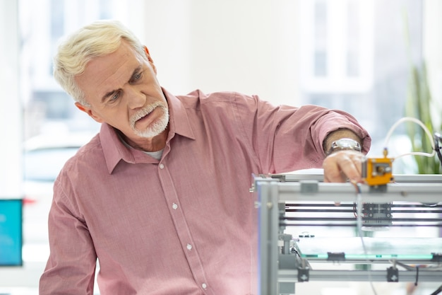 Attrezzature all'avanguardia. affascinante uomo anziano che utilizza una stampante 3d in ufficio e controlla il suo lavoro