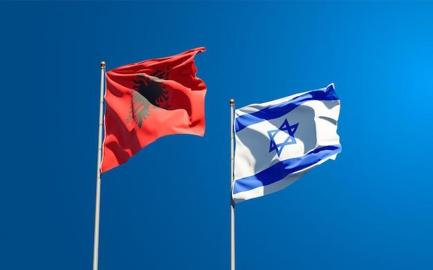 Bandiere di stato di israele e albania insieme sullo sfondo del cielo