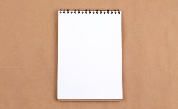 Concetto stazionario, vista dall'alto laico piatta foto del blocco note vuoto su beige