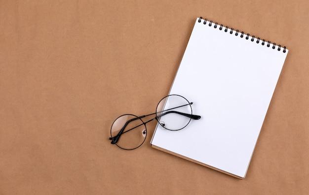 Concetto stazionario, vista dall'alto distesa piatta foto di occhiali e blocco note su beige
