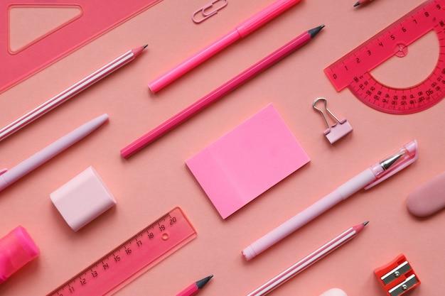 Concetto stazionario, vista dall'alto piatto foto di materiale scolastico forbici, matite, graffette, calcolatrice, nota adesiva, cucitrice e blocco note in colori pastello su sfondo rosa, motivo.