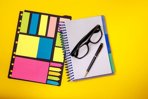 Concetto stazionario. penna, occhiali nota adesiva. forniture per ufficio.