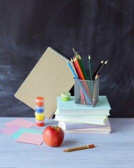 Apple della cancelleria sul concetto di apprendimento del fondo del bordo della scuola torna a scuola