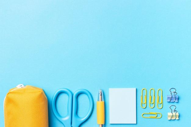 Articoli di cancelleria su uno sfondo blu con una copia dello spazio, il concetto di tornare a scuola