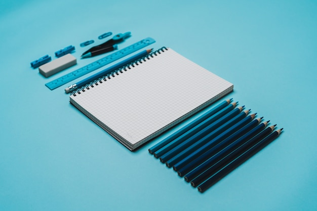 Articoli di cancelleria - libro, matita, righello su sfondo blu.