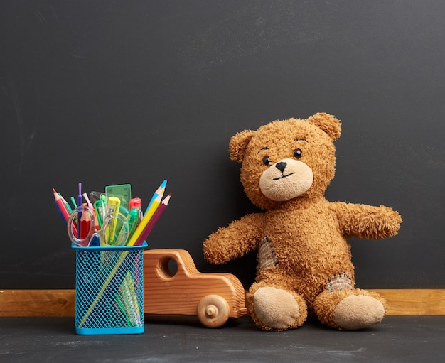 Cancelleria e orsacchiotto marrone seduto sullo sfondo di un bordo di gesso nero vuoto
