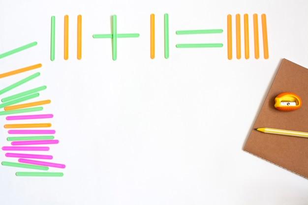 Articoli di cancelleria per matematica, bastoncini per conteggio, taccuino, matita e temperamatite, disposizione piatta, copia spazio