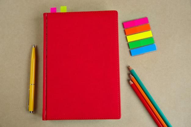 Articoli di cancelleria, taccuino, penna, matite su sfondo di carta artigianale