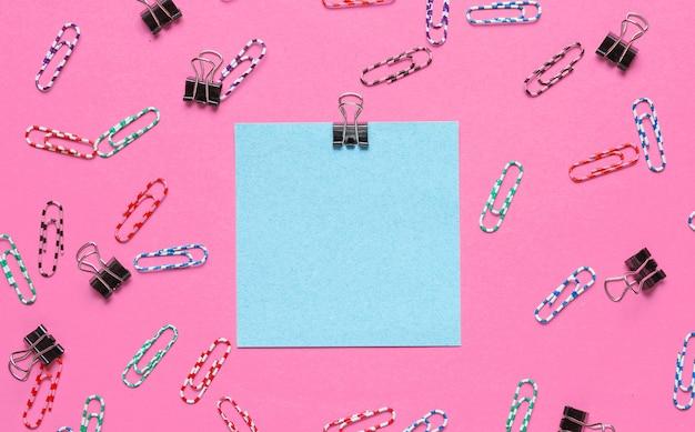 Articoli di cancelleria per ufficio. carta blu per appunti, graffetta sul rosa