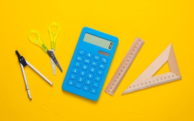 Forbici di cancelleria (scuola), calcolatrice, bussola, righello su giallo