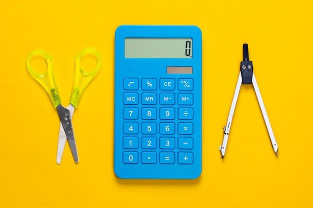 Forbici per cancelleria (scuola), calcolatrice, bussola su giallo