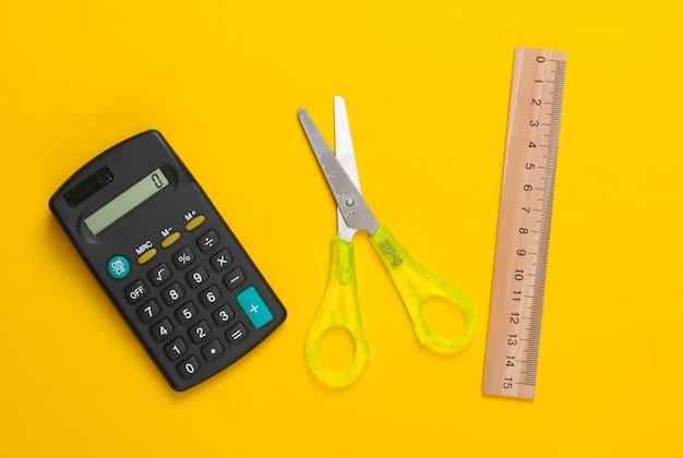 Forbici per cancelleria (scuola), righello, calcolatrice su giallo