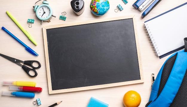 Materiale scolastico di cancelleria intorno al tabellone. vista dall'alto e copia spazio