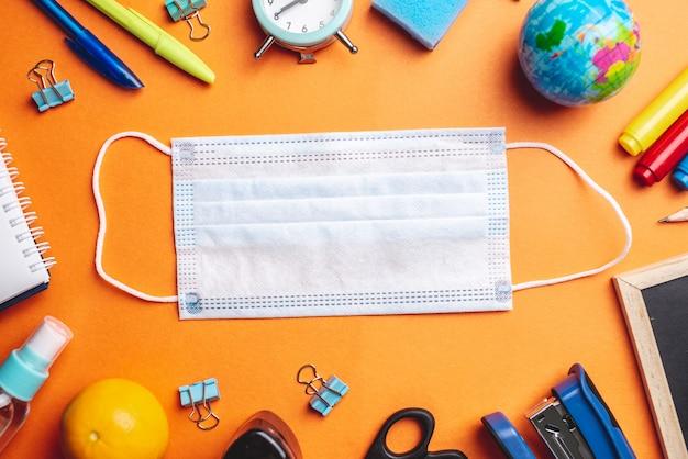 Forniture scolastiche di cancelleria intorno alla mascherina medica sullo sfondo arancione
