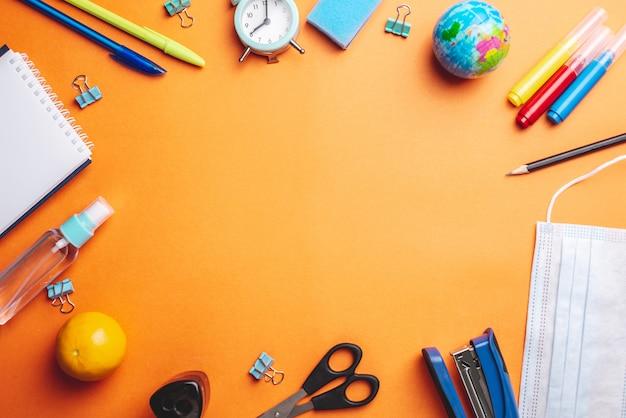 Materiale scolastico di cancelleria, maschera medica e antisettico su uno sfondo arancione