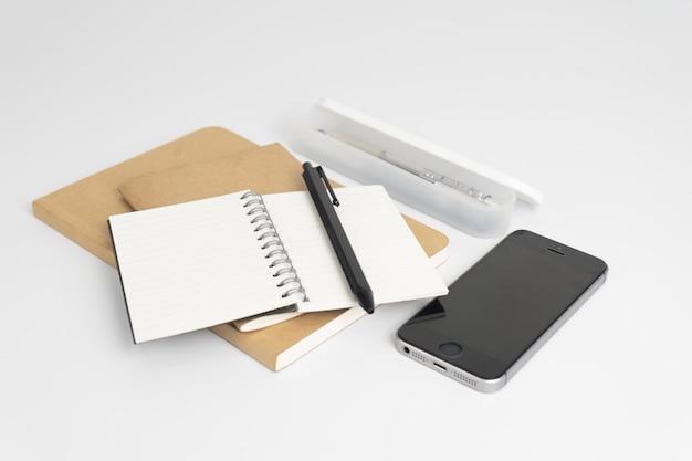 Set di cancelleria come quaderni, penna e smartphone su sfondo bianco.