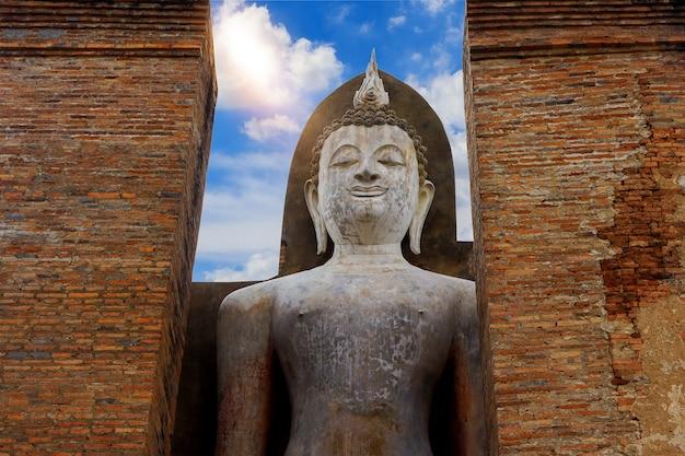 Statua antica del buddha sul cielo blu parco storico di sukhothai
