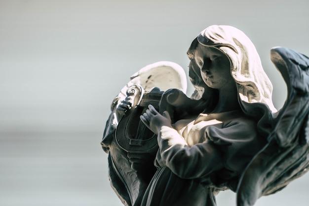 Statua di un angelo che suona l'arpa nel giardino