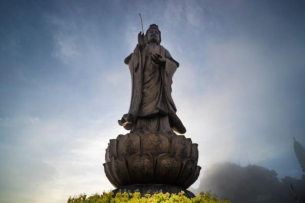 Statua del bodhisattva sul picco di montagna fansipan la montagna più alta in indocina contesto bella vista cielo blu e nuvole a sapa, vietnam.