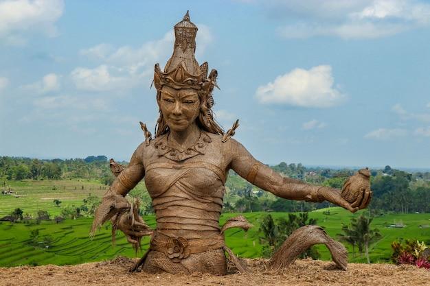 Statua di dewi sri, la dea del riso, realizzata con foglie di piante di riso essiccate, situata nel centro delle terrazze di riso jatiluwih, un sito patrimonio dell'unesco nella parte occidentale di bali