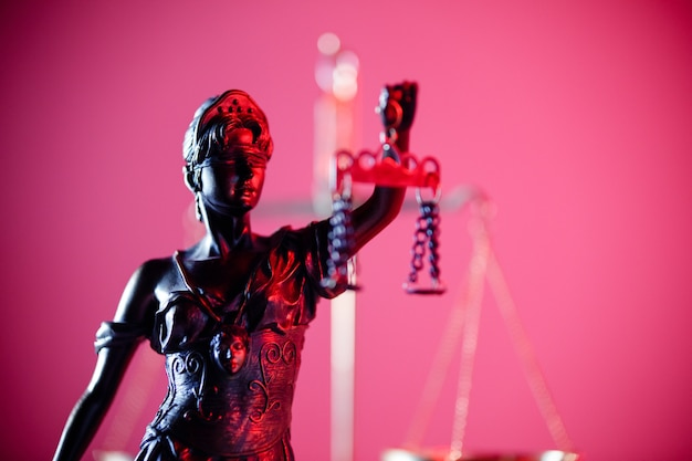 Statua di lady justice nell'ufficio notarile in neon rosso. simbolo di giustizia e diritto.