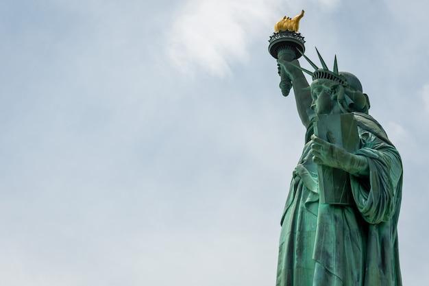 Fine della statua della libertà su in un giorno soleggiato, cielo blu a new york
