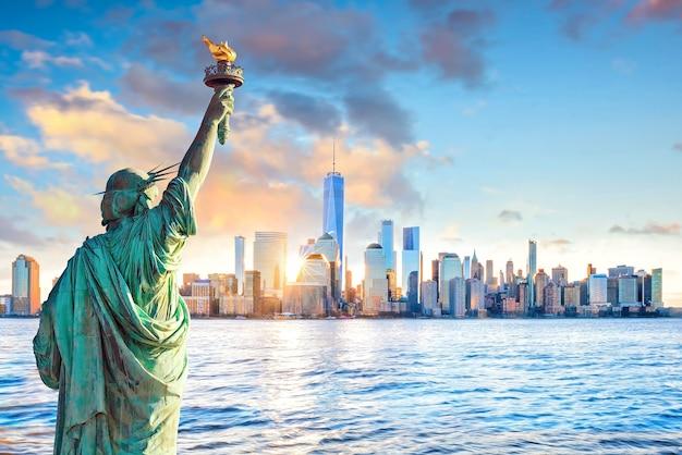 Statua della libertà e dello skyline di new york al tramonto, negli stati uniti