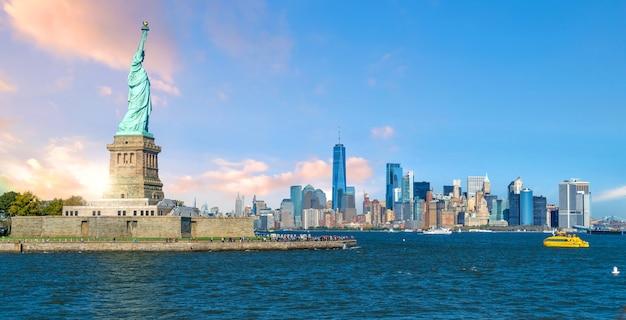 La statua della libertà con lo sfondo dello skyline della città di manhattan, punti di riferimento di new york city, usa