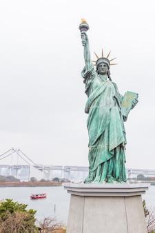 Statua della libertà con rainbow bridge a odaiba, tokyo.