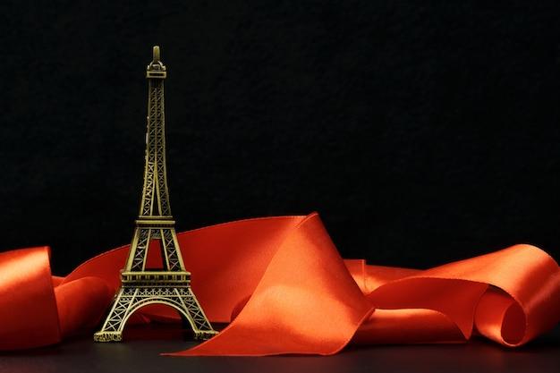 Una statuetta della torre eiffel circondata da un nastro rosso su sfondo nero.