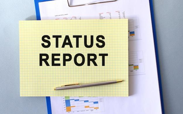 Rapporto di stato testo scritto sul blocco note con la matita