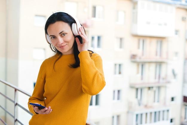 Resta a casa concetto. la donna ascolta musica sul balcone. donna che per mezzo del telefono cellulare e delle cuffie senza fili. autoisolamento a casa.