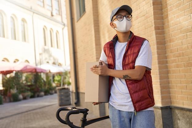 Resta a casa concetto giovane corriere asiatico che indossa una protezione per il viso m