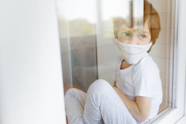Resta a casa in quarantena per prevenire la pandemia di coronavirus. bambino triste sia in maschere mediche protettive vicino a finestre e guarda fuori dalla finestra
