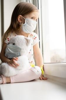 Resta a casa quarantena coronavirus prevenzione pandemia. il bambino triste e il suo orsacchiotto entrambi in maschere mediche protettive si siede sul davanzale della finestra e guarda fuori dalla finestra