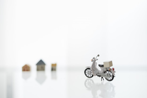 Resta a casa, riparo sul posto con consegna e shopping online concept. primo piano di scotter / moto con scatola contenitore e mini casa come sfondo.