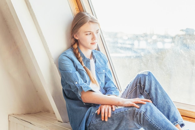 Resta a casa resta al sicuro. giovane ragazza carina in jeans, giacca di jeans e maglietta bianca seduto sul davanzale della finestra nel soggiorno di luce intensa a casa al chiuso e pensando. concetto di distanza sociale jomo.
