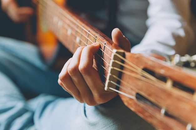 Resta a casa resta al sicuro. la giovane donna che si siede a casa e che gioca la chitarra, mani si chiudono su. ragazza teenager che impara suonare e scrivere musica. lo stile di vita hobby si distende concetto di educazione del tempo libero dello strumento.