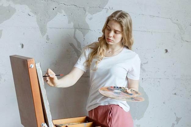 Resta a casa: giovane ragazza con pennello e tavolozza in piedi vicino al disegno a cavalletto