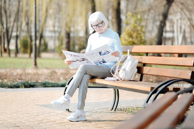 Rimanere informati. grave donna invecchiata leggendo un giornale mentre è seduto sulla panchina