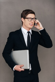 Rimanere in contatto con i colleghi. fiducioso giovane in abbigliamento formale che trasporta laptop e parla al telefono cellulare mentre si trova in piedi su sfondo grigio